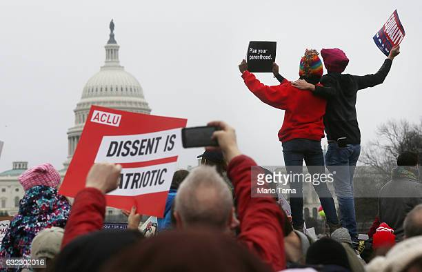 Protesters attend the Women's March on Washington with the US Capitol seen in the background on January 21 2017 in Washington DC Large crowds are...
