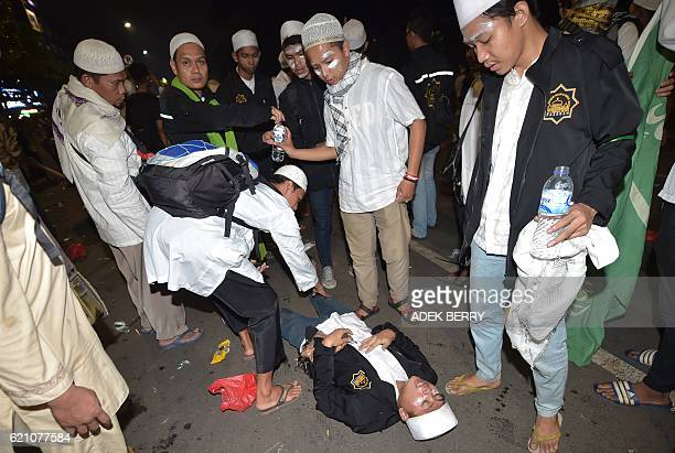 Protesters attend to an injured friend outside the presidential palace after clashes that marred an otherwise peaceful rally against governor Basuki...