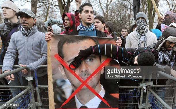 Protesters beat a poster of President Assad with their shoes outside the Syrian Embassy in Belgrave Square in central London demonstrating about the...