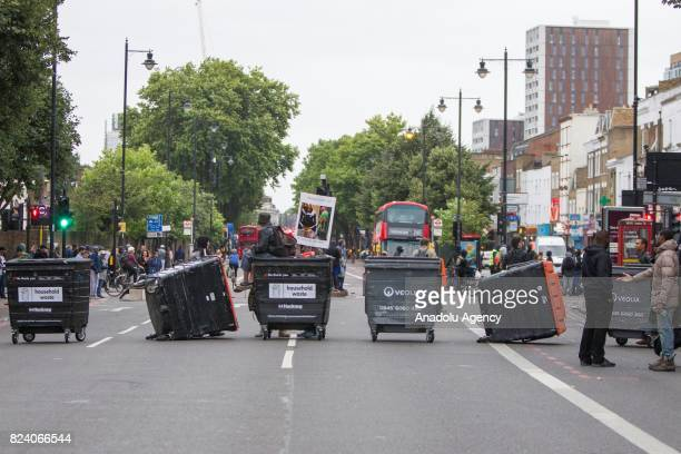 Protesters block a road with trash bins during a demonstration demanding justice after the death of Rashan Charles who was killed last weekend after...