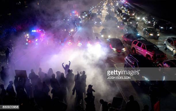 TOPSHOT Protesters block both directions of the Interstate 580 freeway during a rally against racism in Oakland California on August 12 2017...