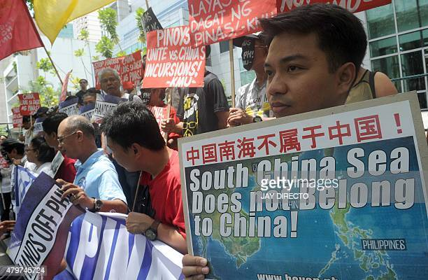 Protesters brandish placards at a rally in front of the Chinese Consulate in Manila's financial district on July 7 denouncing China's claim to most...