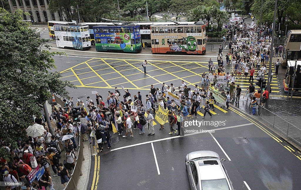 Protesters brave the rain and march toward the US Consulate from Central, Hong Kong in support of Edward Snowden on June 15, 2013 in Hong Kong, Hong Kong. Former CIA employee Edward Snowden is accused of leaking details of top-secret US surveillance of phones and internet.