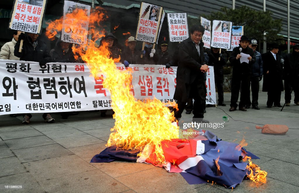 Protesters burn a North Korean national flag during a demonstration against North Korea's nuclear test in Seoul, South Korea, on Tuesday, Feb. 12, 2013. North Korea conducted its third underground nuclear test today, underscoring a disregard for an international community that has already isolated the totalitarian state from the global economy. Photographer: SeongJoon Cho/Bloomberg via Getty Images