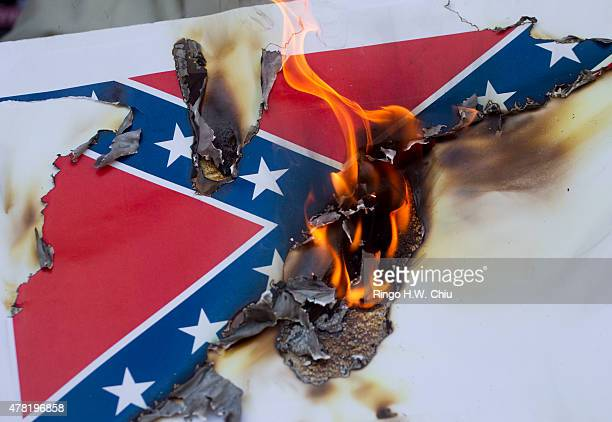 Protesters burn a paper Confederate flag during a rally on June 23 2015 in Los Angeles California The protesters were supporting the call by South...