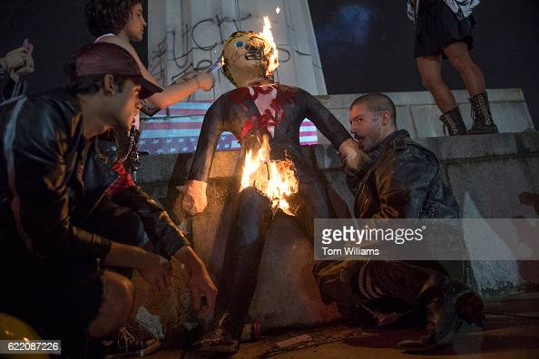 Protesters burn an effigy of Donald Trump in Lee Circle before a march through New Orleans La November 9 2016