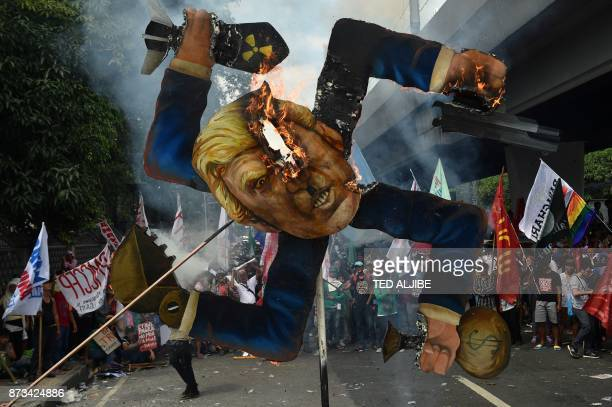 TOPSHOT Protesters burn an effigy of US President Donald Trump during a march to ASEAN Summit venue during the 31st Association of South East Asian...