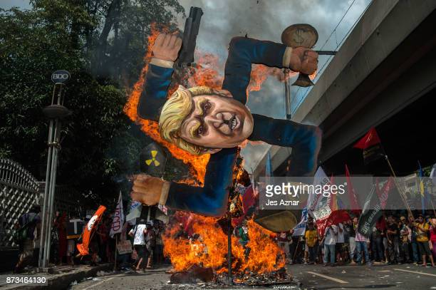 Protesters burn an image of US President Donald Trump fashioned on a swastika as they march the streets of Manila during the start of the ASEAN...