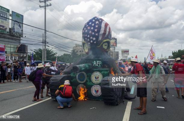 Protesters burn an octopus effigy during a rally coinciding President Rodrigo Duterte's annual State of the Nation Address in Quezon City northeast...