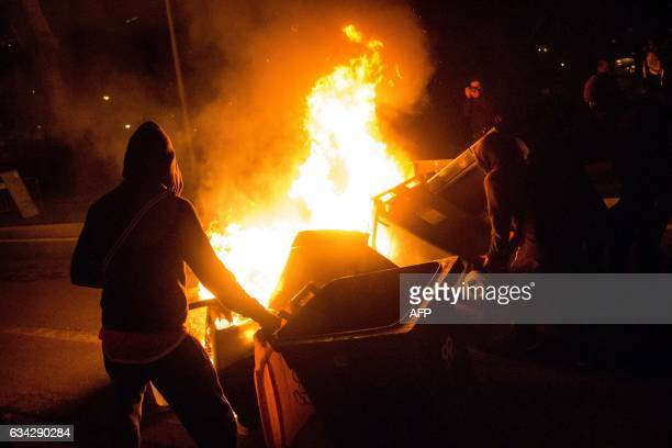 Protesters burn garbage containers during a protest in support of a man allegedly abused while in police custody in AulnaysousBois on February 8 2017...