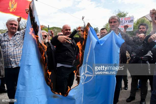 Protesters burn the NATO flag on April 28 2017 during a protest against the Montenegro's accession to NATO in Cetinje Montenegro's parliament...