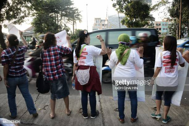 Protesters call out to passing motorists for support outside the Indonesian High Court building in Jakarta on May 12 to demand the release of...