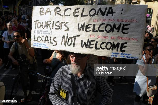 A protesters carry a banner that reads 'Barcelona Tourist welcome locals not welcome' during a demonstration in Barcelona on June 10 2017 against...