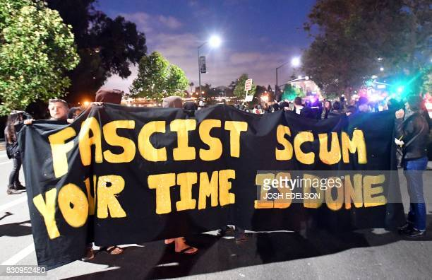 TOPSHOT Protesters carry a banner while taking part in a march against racism in Oakland California on August 12 2017 Protesters marched on the...