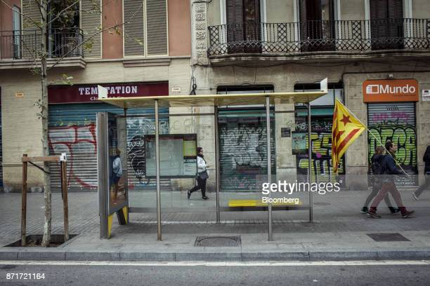 Protesters carry a Catalan Estelada flag past closed stores during a regional strike called by proindependence union in Barcelona Spain on Wednesday...
