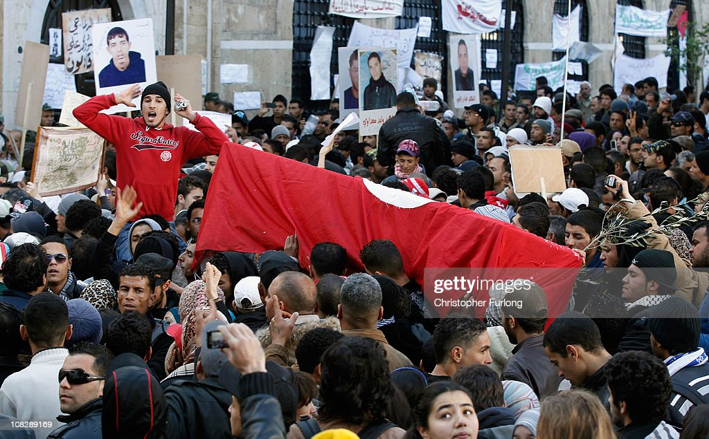 Protesters carry a coffin draped in the Tunisian flag representing martyr Mohamed Bouazizi outside the prime minister's office on January 24 2011 in...
