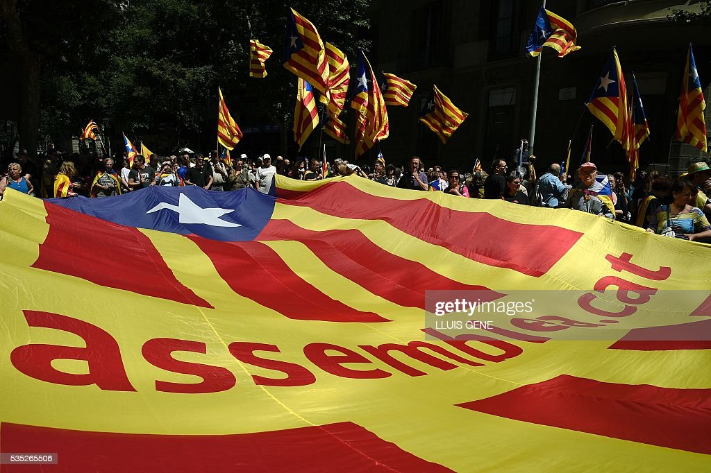 Protesters carry a giant independentist flag during a demonstration called by some 20 social movements, groups and organizations under the slogan, 'Rights, can't be suspended' outside the Catalan government headquarters in Barcelona on May 29, 2016. / AFP / LLUIS