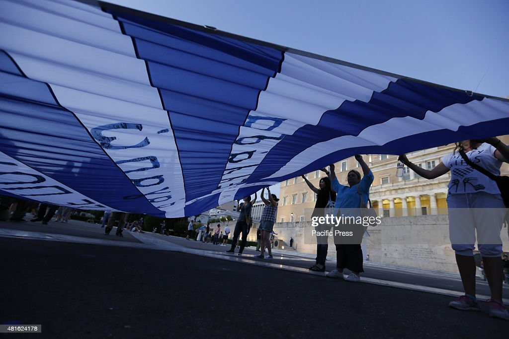 SQUARE ATHENS ATTICA GREECE Protesters carry a large Greek Flag outside the Greek Parliament at the protest against the second tranche of the Greek...