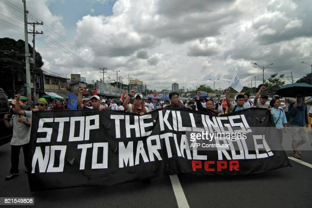Protesters carry anti martial law banners as they gather outside the House of Representatives where Philippine President Rodrigo Duterte's state of...