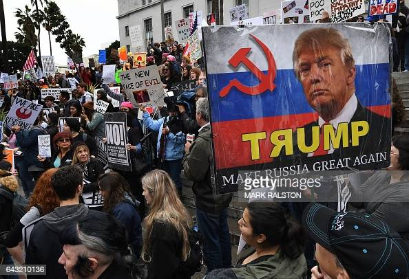 Protesters carry antiTrump signs during a 'Not My President Day' demonstration outside City Hall in Los Angeles California on February 20 2017 / AFP...