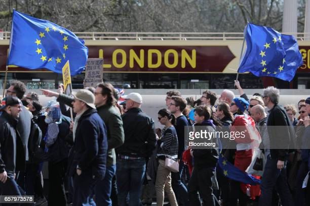 Protesters carry European Union flags past a London sightseeing tour bus during a Unite for Europe march to protest Brexit in central London UK on...