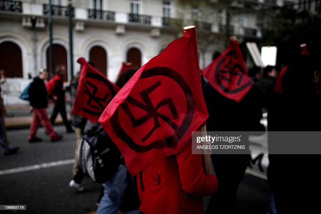 Protesters carry flags against racism, during a demonstration against attacks on immigrants in Athens on November 24, 2012. At least 3,000 leftists and anarchists took part in the Athens protest, an AFP reporter said, chanting slogans against the neo-Nazi group Golden Dawn which rights groups say enjoys protection by racist elements within the police. AFP PHOTO / Angelos Tzortzinis