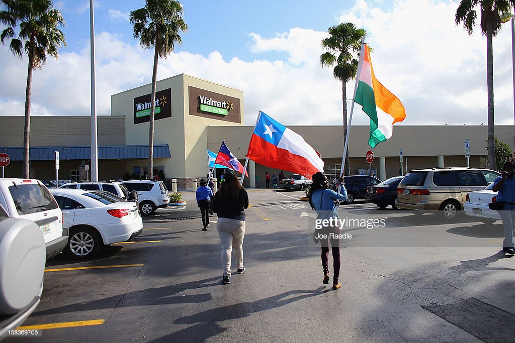Protesters carry flags as they participate in a 'Global Day' of action against Walmart on December 14, 2012 in Hialeah, Florida. The protesters in partnership with the global union federation UNI, the union-affiliated group Making Change at Walmart joined others around the world to among other things call for an end to alleged retaliation against US Walmart worker activists.