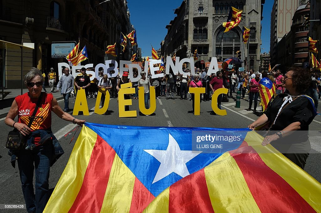 Protesters carry giant lettersto form a message reading, 'Disobedience. Goodbye to TC (Constitutional Court)' during a demonstration called by some 20 social movements, groups and organizations under the slogan, 'Rights, can't be suspended' outside the Catalan government headquarters in Barcelona on May 29, 2016. / AFP / LLUIS