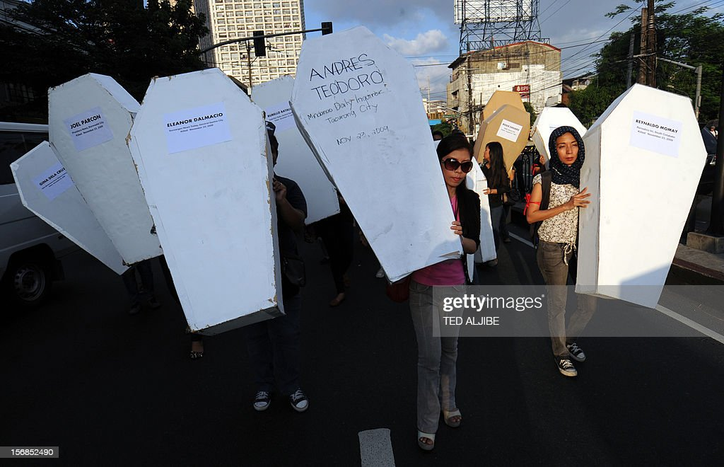 Protesters carry mock coffins during a march protest to Malacanang Palace in Manila on November 23, 2012, to commemorate the third anniversary of the November 23 Maguindanao massacre. Dozens of members of a clan whose leaders are on trial for the Philippines' worst political massacre are candidates in 2013 elections, some for the president's party, media and rights groups said November 23. The revelations sparked outrage on the three-year anniversary of the massacre, in which 58 people died, with critics saying the Ampatuan family's enduring political influence underlined the country's 'culture of impunity'.
