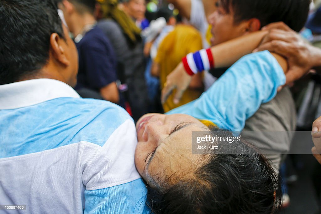 Protesters carry one of their own after she was overcome by tear gas during a large anti government protest on November 24, 2012 in Bangkok, Thailand. The Siam Pitak group, which sponsored the protest, cited alleged government corruption and anti-monarchist elements within the ruling party as grounds for the protest. Police used tear gas and baton charges againt protesters.