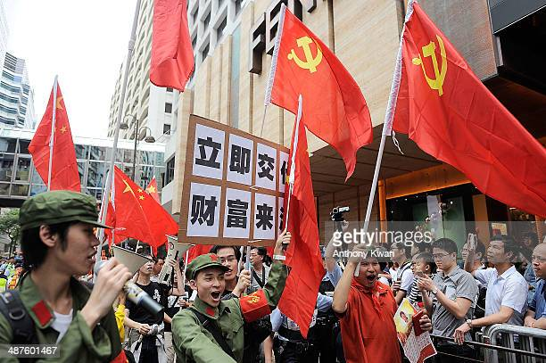 Protesters carry placards and the flags of People's Republic of China and Communist Party of China as they walk on a street during a rally on May 1...