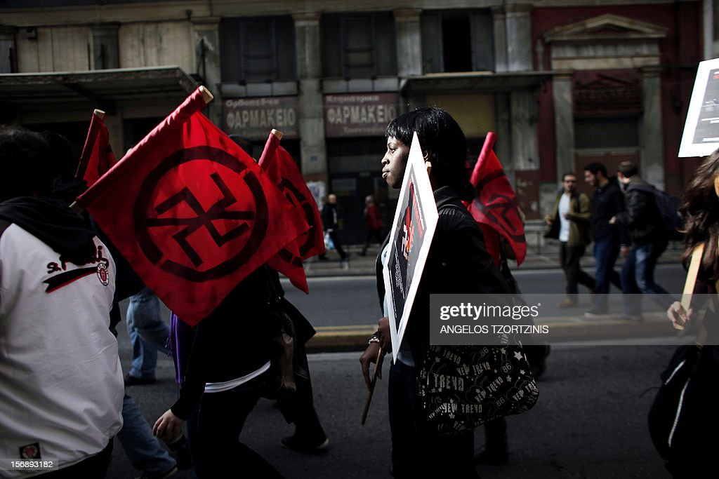 Protesters carry poster and flags against racism, during a demonstration against attacks immigrants in Athens on November 24, 2012. At least 3,000 leftists and anarchists took part in the Athens protest, an AFP reporter said, chanting slogans against the neo-Nazi group Golden Dawn which rights groups say enjoys protection by racist elements within the police. AFP PHOTO / Angelos Tzortzinis