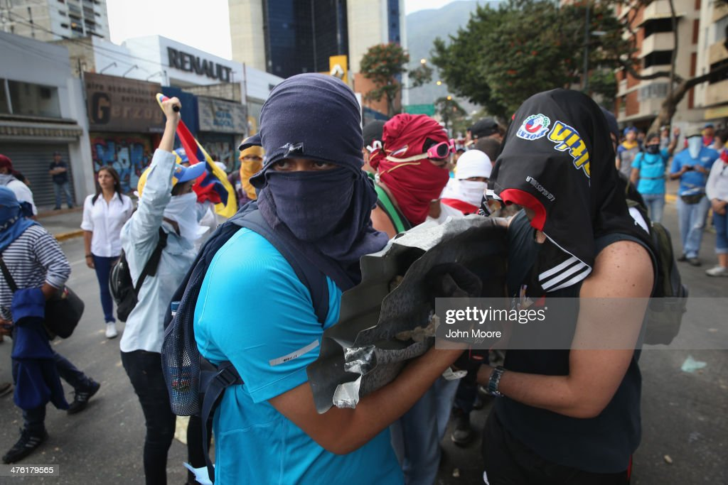 Protesters carry rocks to throw at national guard troops following an anti-government demonstration on March 2, 2014 in Caracas, Venezuela. Venezuela has one of the highest inflation rates in the world, and opposition supporters have protested for almost three weeks, virtually paralyzing business in much of the country.