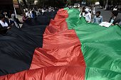 Protesters carry the Afghan national flag as they chant antigovernment slogans during a demonstration in the city of Kabul on July 23 2016 Thousands...