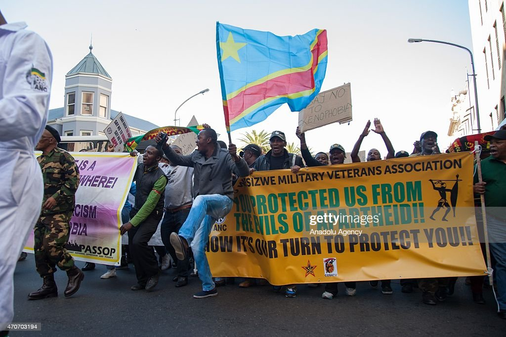 Protesters carry the flag of their own countries and banners as they march towards the Parliament building during an antixenophobia demonstration in...