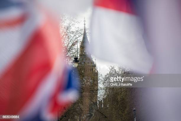 Protesters chant and wave British Union Jack flags as the Houses of Parliament are seen in the background during a protest titled 'London march...
