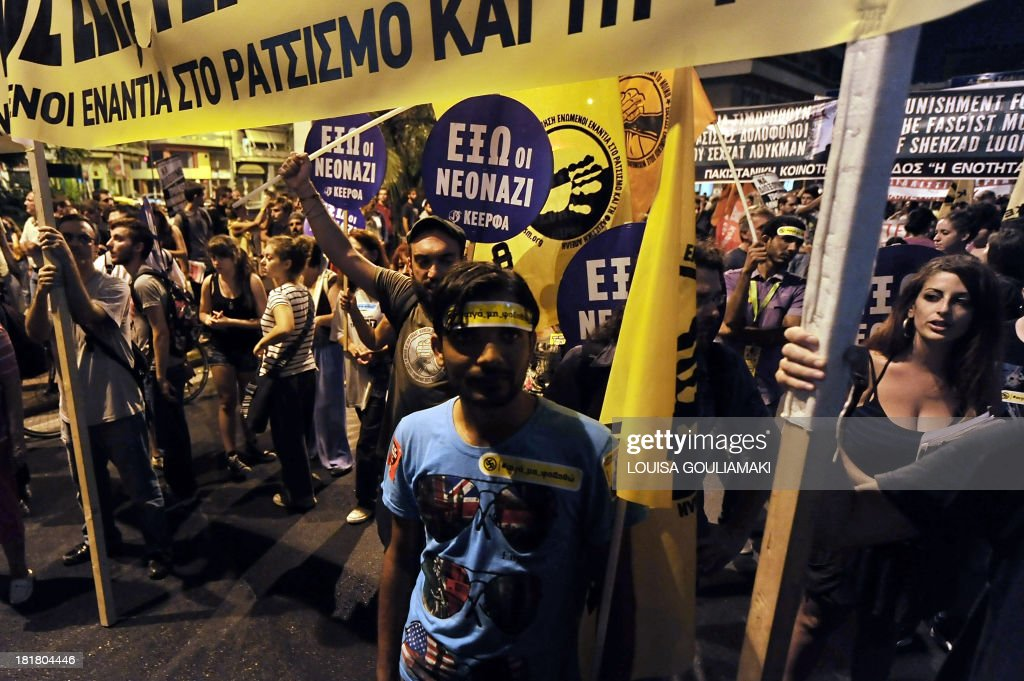 Protesters chant anti-Nazi slogans near a police barricade on September 25, 2013 during a massive demonstration in Athens heading toward the offices of the neo-Nazi party Golden Dawn. Greek Police clashed with protesters in Athens late September 25 at the end of a huge march sparked by the murder of an anti-fascist musician, allegedly at the hands of a self-confessed neo-Nazi. Protesters were seen hurling petrol bombs at riot police, who responded with tear gas a few hundred meters (yards) from the headquarters of the Golden Dawn.