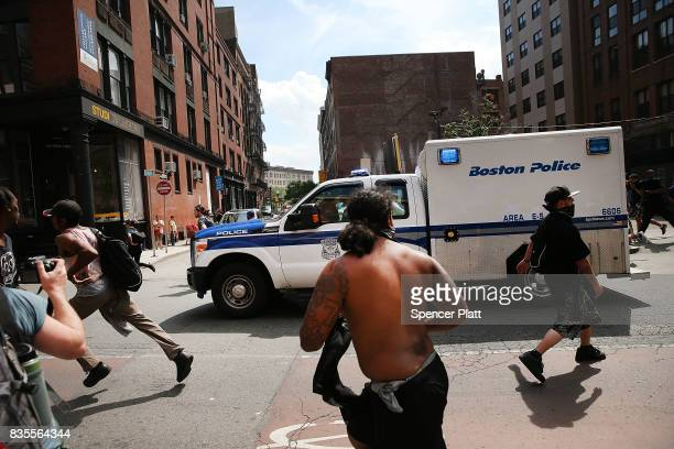 Protesters chase a police van escorting conservative activists out of the city following a march in Boston against a planned 'Free Speech Rally' just...
