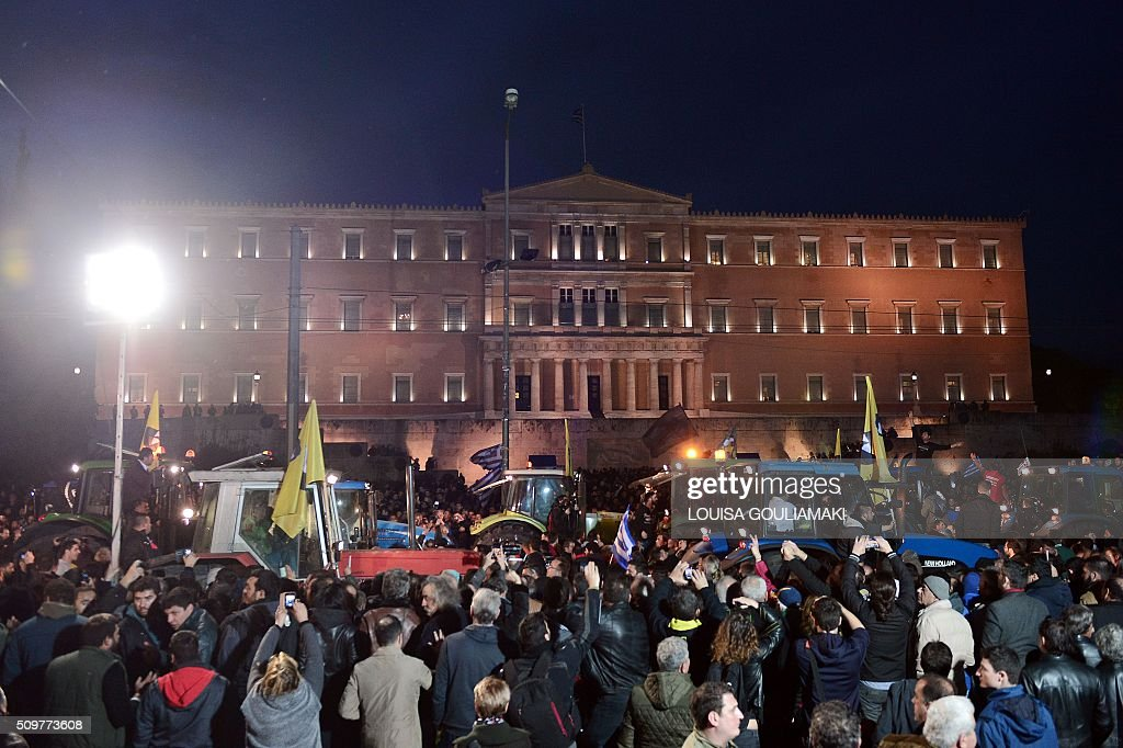 Protesters cheer as farmers on their tractors arrive in front of the Greek parliament in Athens during their rally against pension reform,on February 12, 2016. Fears that Greece will exit the eurozone, a 'Grexit', could revive if Greek authorities do not come up with 'credible' reforms, notably on pensions, a senior IMF official said February 11. / AFP / LOUISA GOULIAMAKI