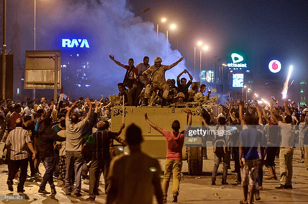 Protesters cheer upon the arrival of the Egyptian Security Forces during clashes between demonstrators for and against ousted president Mohamed Morsi...