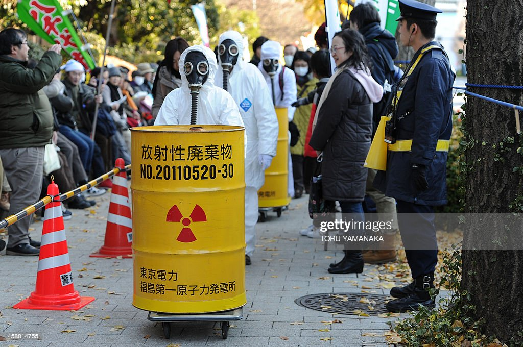 Protesters clad in protective suits carry barrels of mock nuclear waste during a rally denouncing the Japanese government direction to resume nuclear power plants in front of the national Diet in Tokyo on December 22, 2013. Several thousands of people gathered at the rally againt nuclear power plants around the Diet. AFP PHOTO/Toru YAMANAKA