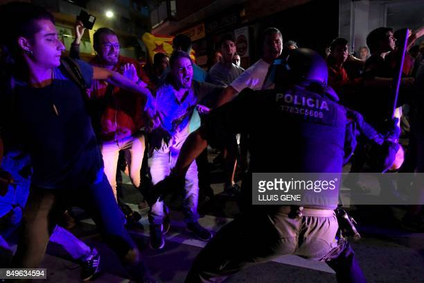 Protesters clash with a Catalan regional police officer 'Mosso D'Esquadra' during a protest against a search for propaganda supporting Catalonia's...