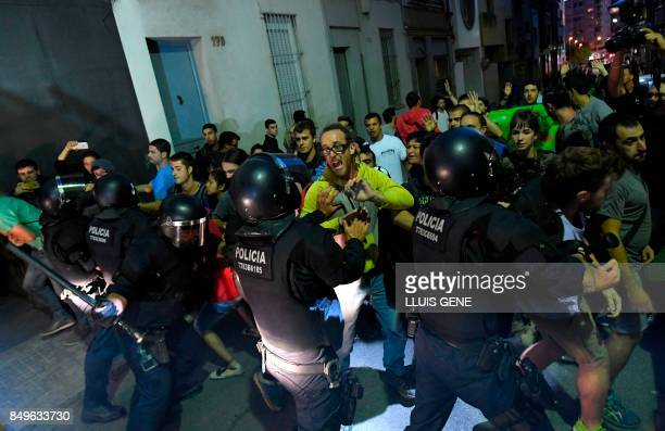 TOPSHOT Protesters clash with Catalan regional police officers 'Mossos D'Esquadra' during a protest against a search for propaganda supporting...