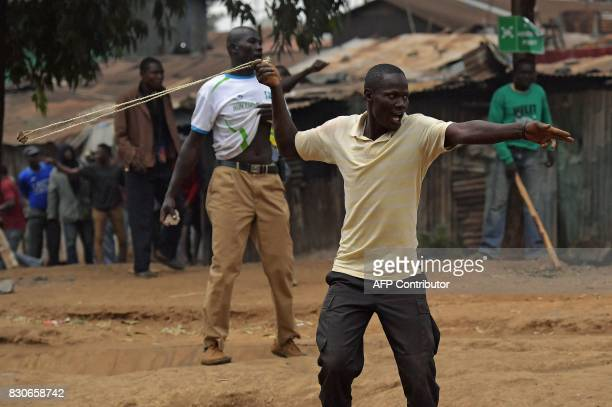 TOPSHOT Protesters clash with Kenyan police forces in Kibera slum in Nairobi on August 12 following the announcement of the election victory of...