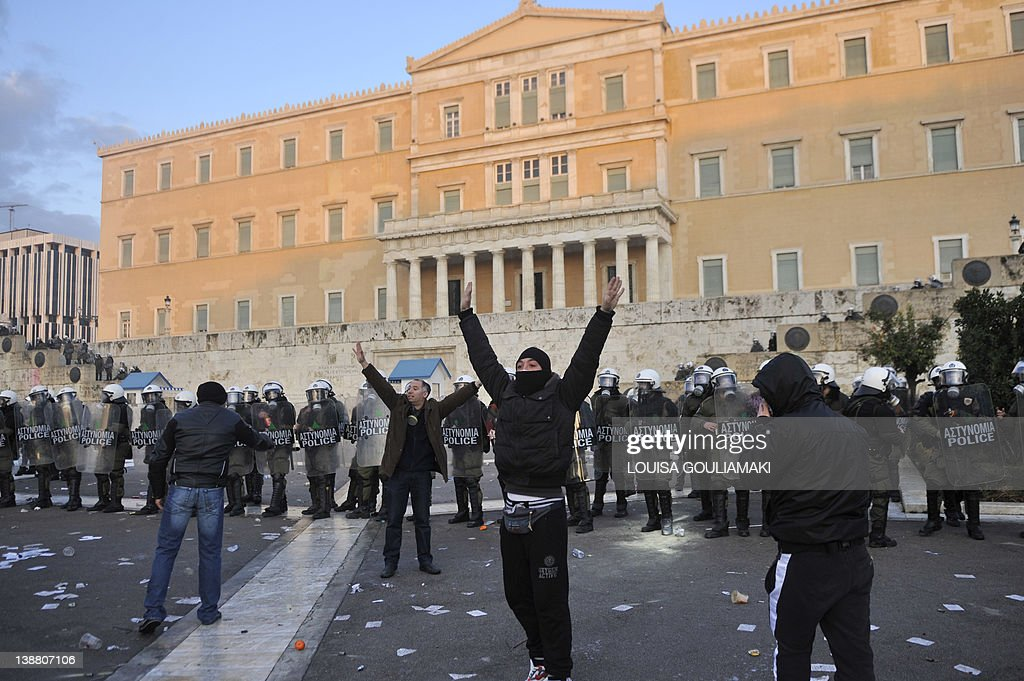Protesters clash with riot police in front of the Parliament in Athens on February 12, 2012. Greek police on Sunday used tear gas on petrol bomb-throwing protesters outside parliament where lawmakers were debating a new austerity plan aimed at staving off bankruptcy.Police said some 25,000 protesters were massed outside the building and at nearby Omonia Square, with some 3,000 police deployed and more protesters arriving..