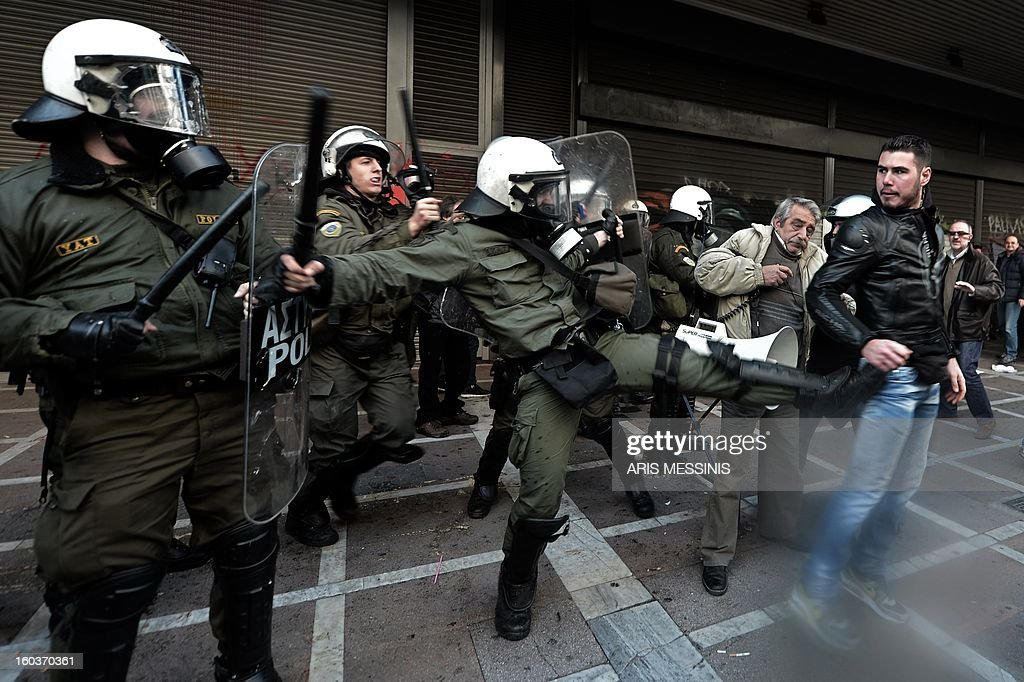 Protesters clash with riot police outside the Labour Ministry in Athens on January 30, 2013. Police were called in on Wednesday to dislodge around 30 Communist unionists from the labour ministry in a protest against new pension cut plans. The unionists were arrested and police used tear gas outside the building to disperse a larger group of protesters demanding their release. AFP PHOTO / ARIS MESSINIS
