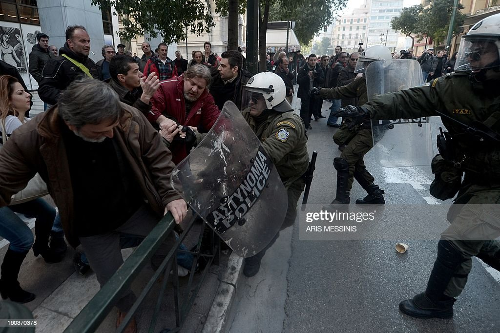 Protesters clash with riot police outside the Labour Ministry in Athens on January 30, 2013. Police were called in on Wednesday to dislodge around 30 Communist unionists from the labour ministry in a protest against new pension cut plans. The unionists were arrested and police used tear gas outside the building to disperse a larger group of protesters demanding their release.