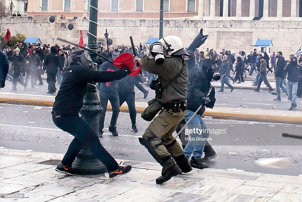 Protesters clash with riot policemen during a 24-hour nationwide general strike on February 4, 2016 in Athens, Greece. Clashes have broken out between Greek police and youths throwing fire bombs and stones, as tens of thousands of people march through central Athens to protest planned pension reforms.