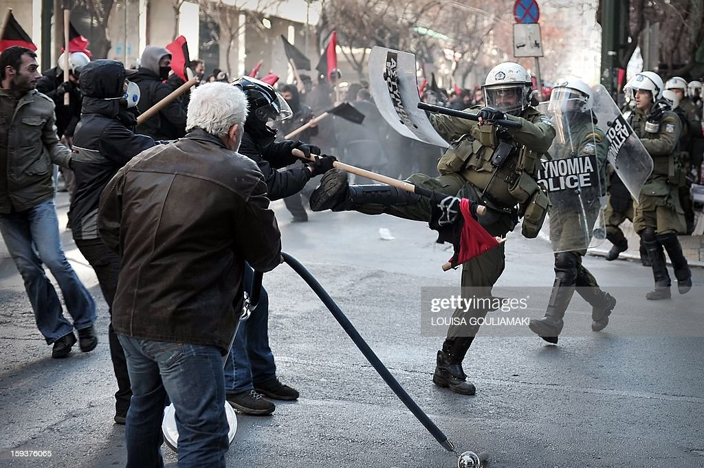 Protesters clash with the riot police during a demonstration in Athens on January 12, 2013. Several thousand people demonstrated in Athens to protest recent police operations against squatters in public buildings that have been condemned by the opposition. The protesters -- estimated by police at around 3,500 and nearly double that by media -- marched to the Athens court complex and police headquarters to demand the release of scores of individuals arrested in the sweeps. One of the central Athens buildings, a 19th-century former school, had been occupied for over two decades. The other is a stately block of flats whose former occupants include legendary soprano Maria Callas before her rise to fame. AFP PHOTO/ LOUISA GOULIAMAKI