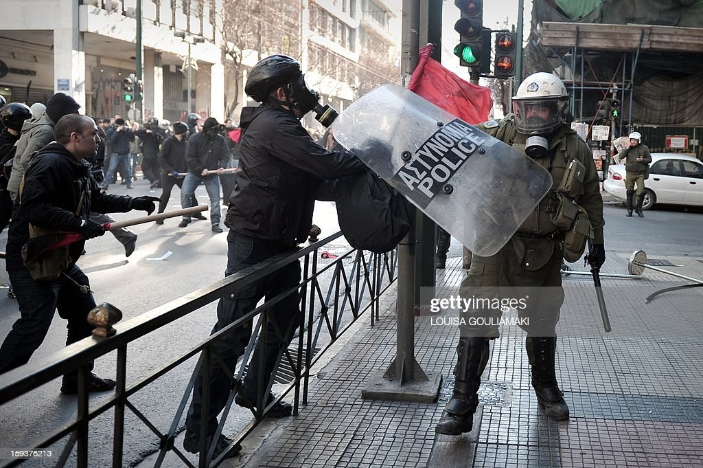 Protesters clash with the riot police during a demonstration in Athens on January 12, 2013. Several thousand people demonstrated in Athens to protest recent police operations against squatters in public buildings that have been condemned by the opposition. The protesters -- estimated by police at around 3,500 and nearly double that by media -- marched to the Athens court complex and police headquarters to demand the release of scores of individuals arrested in the sweeps. One of the central Athens buildings, a 19th-century former school, had been occupied for over two decades. The other is a stately block of flats whose former occupants include legendary soprano Maria Callas before her rise to fame.